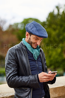 Buy stock photo Shot of a young man using a cellphone while standing on a bridge in Paris