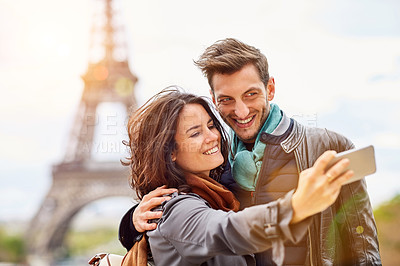 Buy stock photo Shot of a happy young couple talking a selfie together in front of the Eiffel Tower