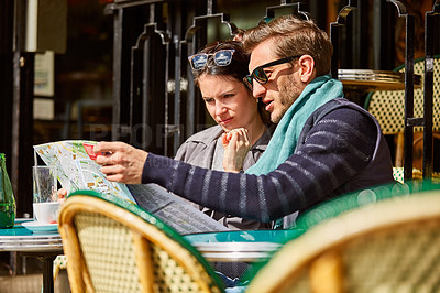 Buy stock photo Shot of a young couple sitting together at a table at a sidewalk cafe in Paris reading a map