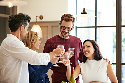 Buy stock photo Shot of two couples talking and toasting together while enjoying a get-together at home