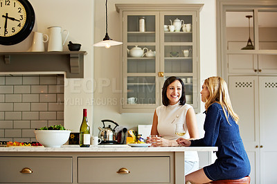 Buy stock photo Shot of two friends talking together while sitting in the kitchen at home