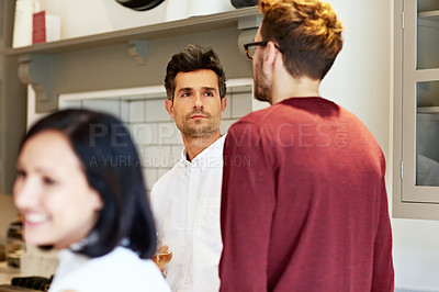 Buy stock photo Shot of two young men drinking wine and talking together in a kitchen at a get-together
