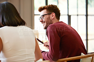 Buy stock photo Shot of a young man enjoying the conversation over dinner