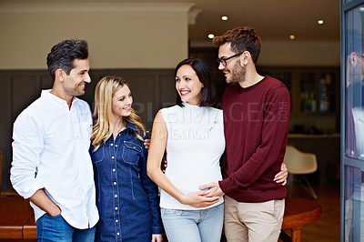 Buy stock photo Shot of a group of friends talking together in a kitchen at a get-together