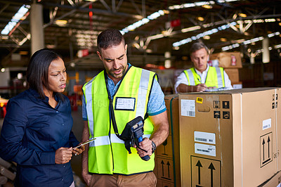 Buy stock photo Shot of two coworkers looking at a barcode reader while standing in a large warehouse