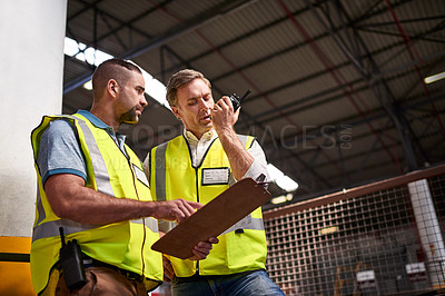 Buy stock photo Shot of two warehouse workers discussing paperwork while standing in a large warehouse