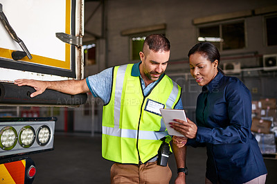 Buy stock photo Shot of a manager holding a digital tablet and talking to a truck driver on the loading dock of a large warehouse