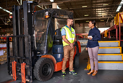 Buy stock photo Shot of two coworkers talking together beside a forklift while standing in a large warehouse