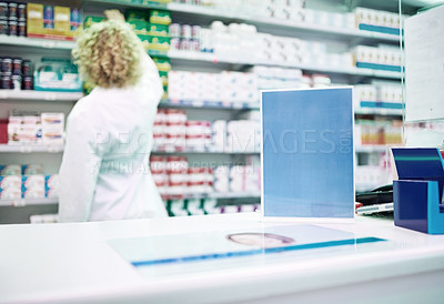 Buy stock photo Shot of a blank board on the counter of a pharmacy with a pharmacist working in the background