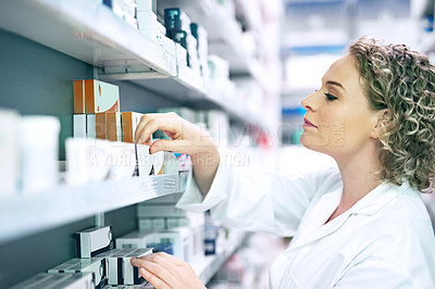Buy stock photo Shot of a pharmacist looking through the shelves at a chemist