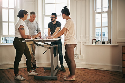 Buy stock photo Shot of a team of designers brainstorming together around a drafting table