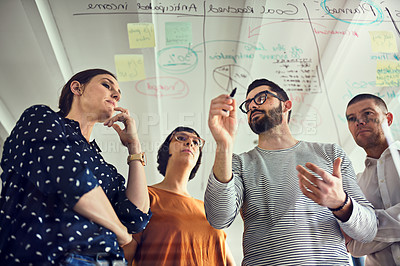 Buy stock photo Shot of a group of young designers working on a transparent wipe board
