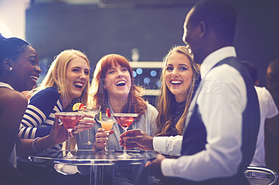 Buy stock photo Shot of a cocktail waiter serving drinks to a group of friends in a nightclub