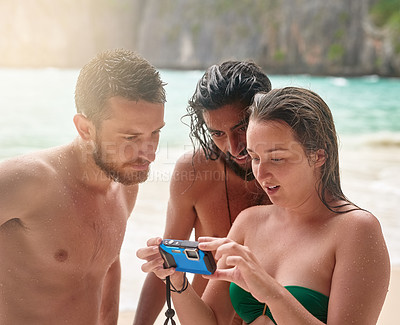 Buy stock photo Cropped shot of three young friends looking at photographs at the beach