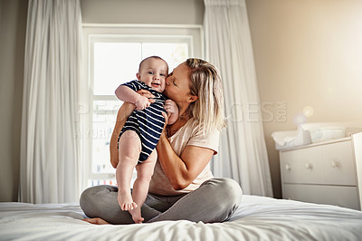 Buy stock photo Full length shot of a mother sitting on a bed at home with her son
