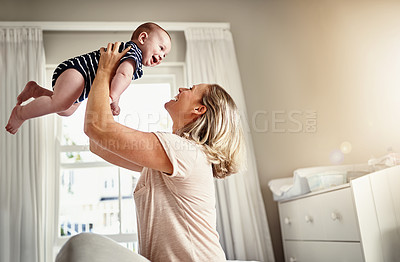 Buy stock photo Cropped shot of a mother sitting on a bed at home with her son