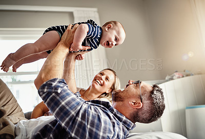 Buy stock photo Cropped shot of a family of three bonding on a bed at home