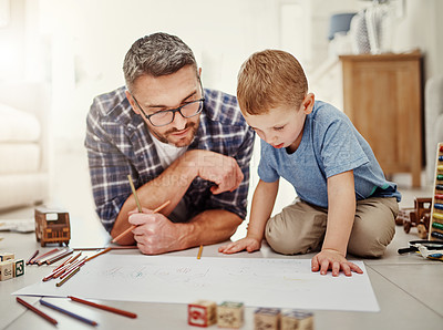 Buy stock photo Shot of a father bonding with his son while drawing at home
