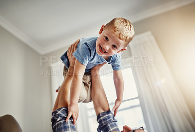 Buy stock photo Cropped portrait of a young boy bonding with his father at home