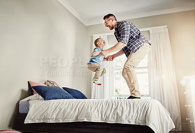 Buy stock photo Full length shot of a father and son jumping on a bed at home