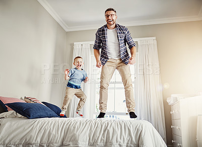 Buy stock photo Full length portrait of a father and son jumping on a bed at home