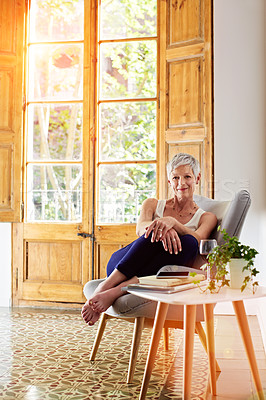 Buy stock photo Portrait of a smiling mature woman relaxing on a chair at home with a glass of wine