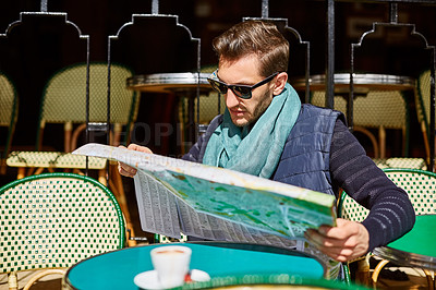 Buy stock photo Shot of a young man reading a map while sitting at a table at a sidewalk cafe
