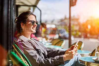 Buy stock photo Shot of a smiling young woman sitting at a sidewalk cafe in Paris using a digital tablet