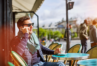 Buy stock photo Shot of a young man sitting at a sidewalk cafe in Paris talking on a cellphone