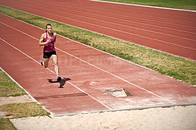 Buy stock photo Shot of a young man running down a track to do a long jump on a sports field