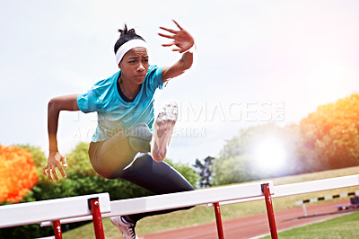 Buy stock photo Shot of a young woman in mid air while jumping over a hurdle on a sports field
