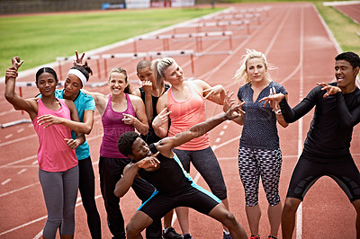 Buy stock photo Portrait of a group of carefree friends in sports clothing standing on a running track