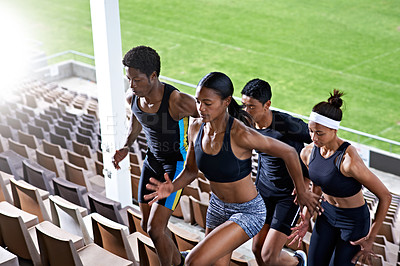 Buy stock photo Shot of a group of young athletes running up stairs in a sports stadium