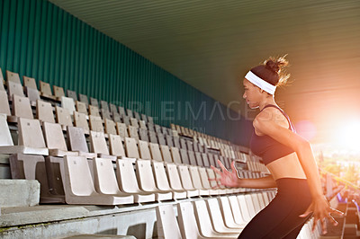 Buy stock photo Shot of a young woman running up stairs in a sports stadium