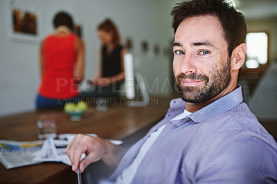 Buy stock photo Portrait of a smiling man sitting at a desk in an office with colleagues working in the background
