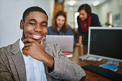 Buy stock photo Portrait of a smiling young man sitting at a desk in an office with colleagues working in the background