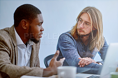 Buy stock photo Shot of two young colleagues talking together while working on a laptop at a desk in an office
