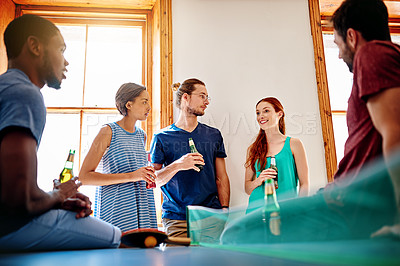 Buy stock photo Shot of a group of colleagues talking and drinking beers together while winding down after work