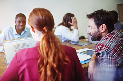 Buy stock photo Shot of a group of colleagues working together around a table in an office