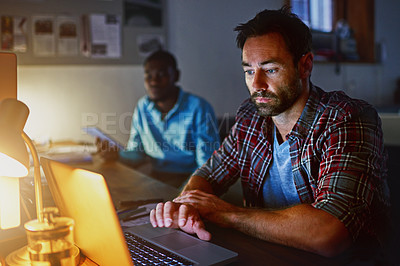Buy stock photo Shot of a man working on a laptop in an office in the evening with colleagues in the background