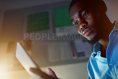 Buy stock photo Shot of a young man working on a digital tablet in an office in the evening