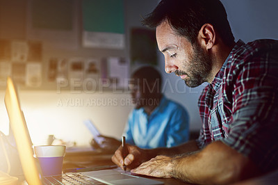 Buy stock photo Shot of a man writing notes while working on a laptop in an office late in the evening