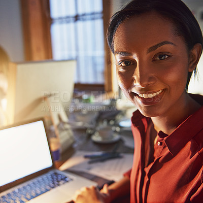 Buy stock photo Portrait of a smiling young woman working on a laptop in an office in the evening