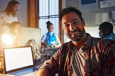 Buy stock photo Portrait of a smiling man working on a laptop in an office in the evening
