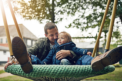 Buy stock photo Shot of a father sitting with his son on a swing outside