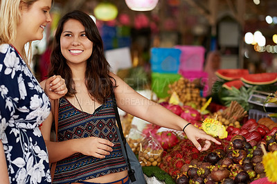 Buy stock photo Cropped shot of two young women looking at fruit in a foreign grocery store