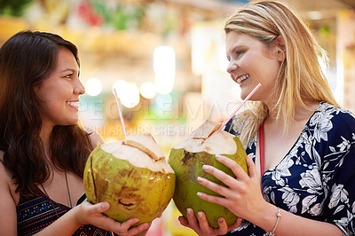 Buy stock photo Cropped shot of two young women drinking from coconuts in a foreign grocery store