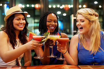 Buy stock photo Cropped shot of three young girlfriends toasting in a bar