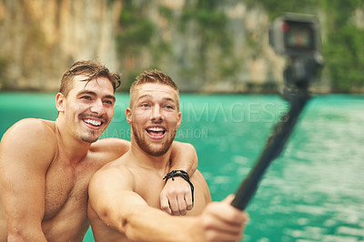 Buy stock photo Cropped shot of two young guys taking a selfie while out for a swim