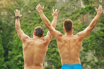 Buy stock photo Rearview shot of two young men jumping into the ocean